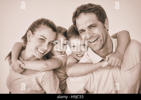 Smiling young family looking at camera together - Stock Photo