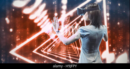 Composite image of rear view of businesswoman holding virtual glasses on a white background - Stock Photo