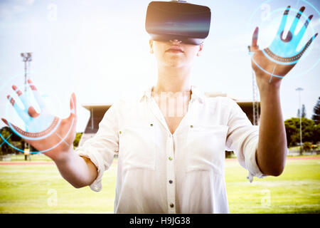 Composite image of woman using a virtual reality device - Stock Photo
