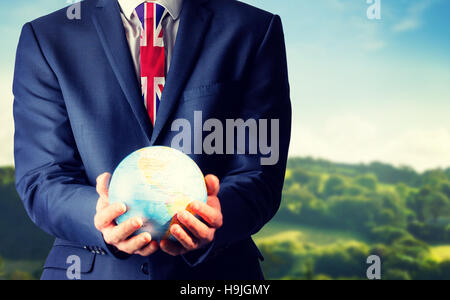 Composite image of hand of businessman holding terrestrial globe - Stock Photo