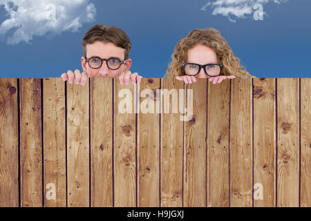 Composite image of geeky hipster couple holding poster - Stock Photo