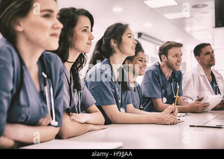 Medical students listening sitting at desk - Stock Photo