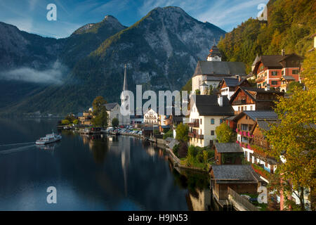 Ferry and first light of dawn over town of Hallstatt and Hallstattersee, Saltzkammergut, Austria - Stock Photo