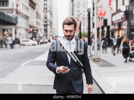 USA, New York City, businessman walking in Manhattan looking at cell phone - Stock Photo