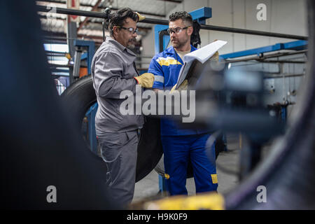Two tire repairmen with clipboard talking - Stock Photo