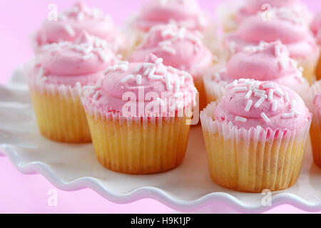 Delicate sweet mini strawberry cupcakes on white pedestal cake stand on pink background in horizontal format.  Shallow - Stock Photo