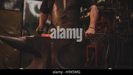 Blacksmith working on hot metal using hammer to shape - Stock Photo