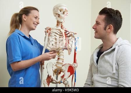 Osteopath Discussing Injury With Patient Using Skeleton - Stock Photo