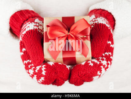Female hands holding christmas gift in red mittens - Stock Photo