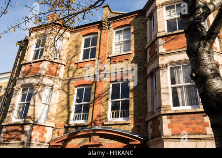 Facade of a traditional British Victorian tenement flat built in bricks - Stock Photo