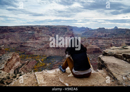 A woman sits on a cliff looking over the San Rafael River and the Little Grand Canyon. - Stock Photo