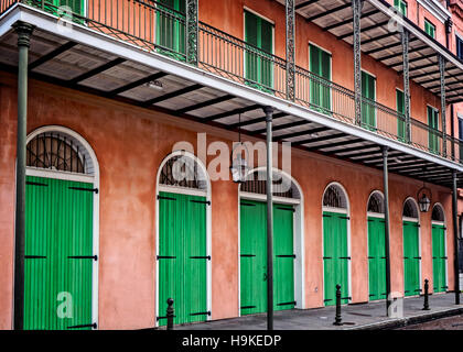 Pink Building with Green Doors and Shutters in the French Quarter  New Orleans - Stock Photo