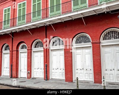 Red Building with White Doors and Green Shutters in the French Quarter in New Orleans - Stock Photo