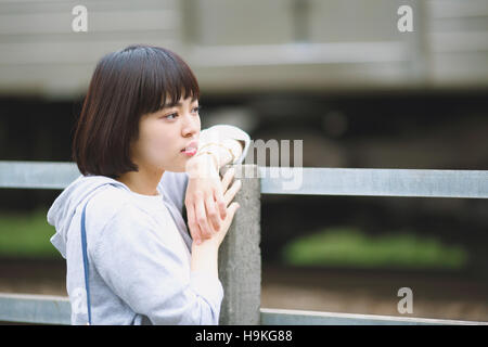 Young Japanese woman by a railway track outside - Stock Photo
