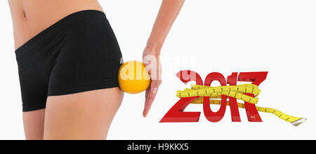 3D Composite image of female buttocks with orange rolling on it - Stock Photo