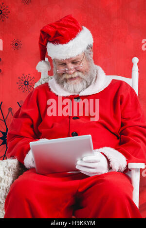 Composite image of santa claus playing games on digital tablet - Stock Photo