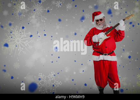 Composite image of smiling santa claus playing guitar - Stock Photo