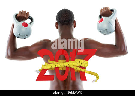 3D Composite image of rear view of shirtless fit man lifting kettle bells - Stock Photo