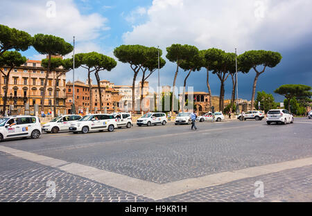 Taxi's lined up waiting for customers along a busy main road in Rome, Italy. - Stock Photo