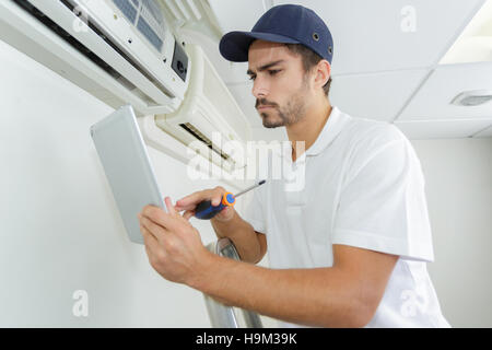 young contractor working carefully and seriously at clients office - Stock Photo