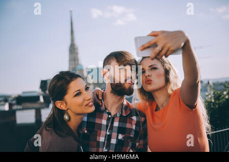 Austria, Vienna, three friends taking selfie on rooftop terrace with Stephansdom in the background - Stock Photo