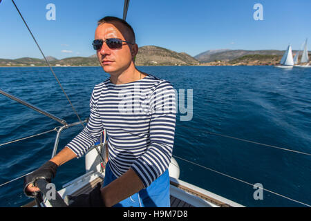 Skipper at the helm controls of a sailing yacht. - Stock Photo