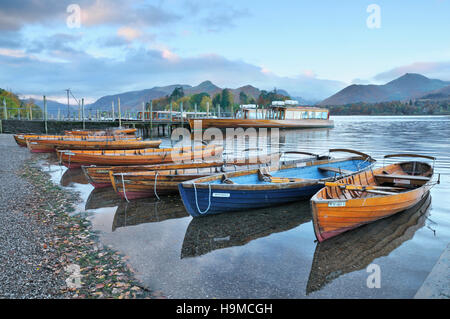 Classic view of wooden boats on Derwentwater at sunrise set against Catbells and Causey Pike, Keswick, Lake District, - Stock Photo