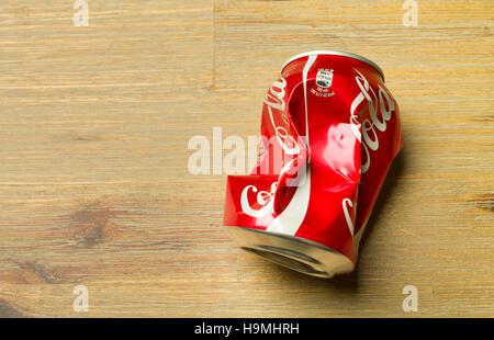 TALLINN, HARJUMAA ESTONIA - NOVEMBER 6, 2016: Crushed classic Coca-Cola can on a desk. - Stock Photo
