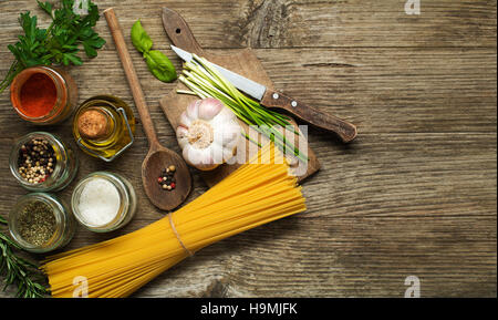 Pasta with spices and ingredients on old wooden table - Stock Photo