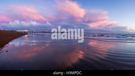 Panorama of Pink clouds around Brighton Palace Pier - Stock Photo