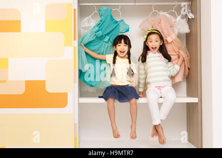 The cute little girl sitting in the closet - Stock Photo