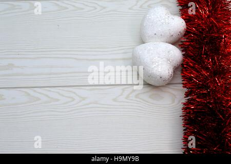Red garland with two white hearts on wooden background - Stock Photo