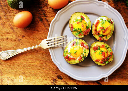 Avocado Egg Boats with bacon on wooden table - Stock Photo