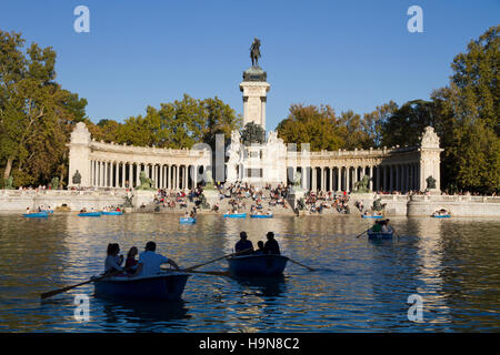 Madrid Spain Retiro, tourists people on boat lake Monument to King Alfonso XII, scene Park del Buen Retiro - Stock Photo