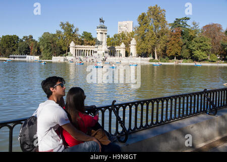 Madrid Spain Park of Retiro couple of tourists visiting day Monument to King Alfonso XII on backgroud - Stock Photo