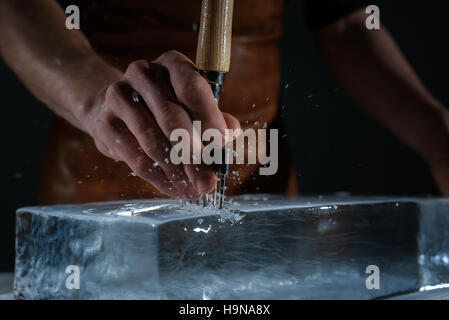 Bartender chopping ice using a special knife - Stock Photo