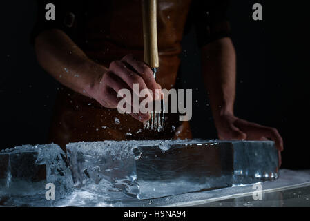 Bartender chopping ice using a special knife. Peaces of ice goes around - Stock Photo