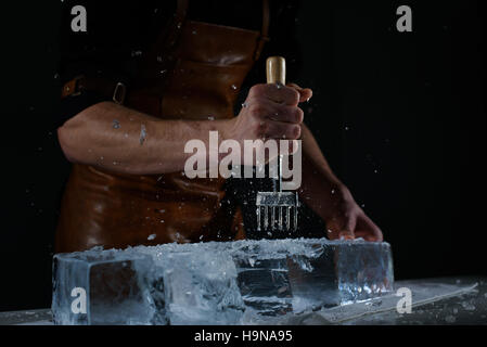 Bartender chopping ice using a special knife. Сhunks of ice flying around - Stock Photo