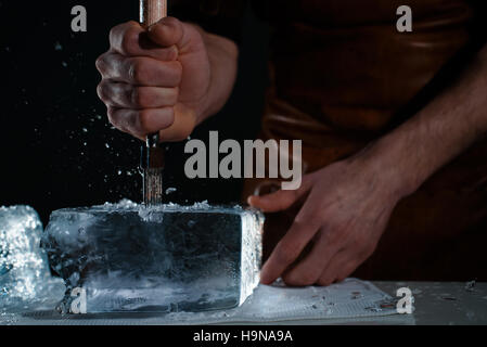 Barman chopping ice using a special knife. Сhunks of ice flying around - Stock Photo