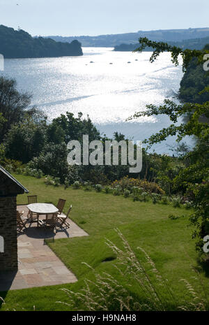 River view, estuary, water reflections, garden with furniture. sun on water - Stock Photo