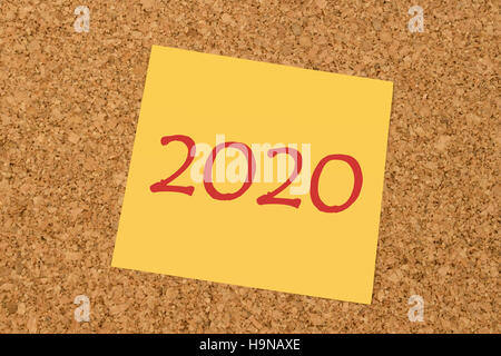 Yellow sticky note on an office cork board - New Year 2020 - Stock Photo