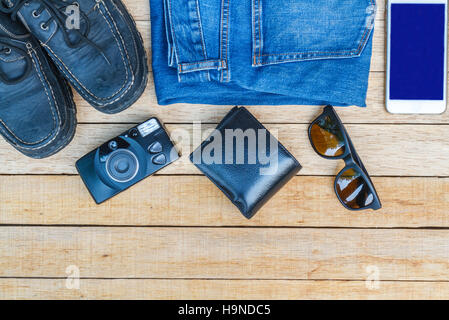 Travel casual outfits with camera, smartphone, shoes, sunglasses, wallet and jean on wooden table. travel concept, - Stock Photo
