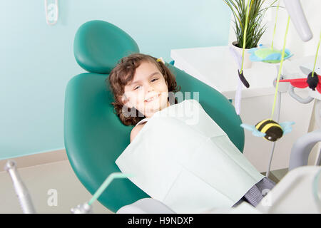 Little cute girl smiling while sitting in chair at dental clinic - Stock Photo