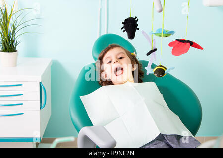 Little cute girl sitting in chair at dental clinic - ready for dentist examining her teeth - Stock Photo