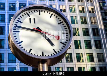 Public clock in Canary Wharf, London against office building - Stock Photo