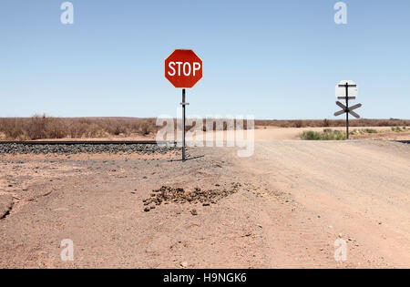 Stop sign in Namibia where a gravel road crosses a railway line - Stock Photo
