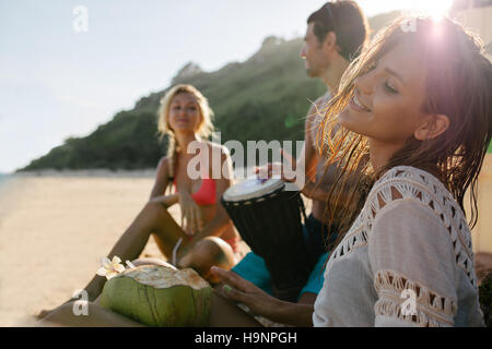 Young woman relaxing on the sea shore with her friends in background. Friends partying and having fun on the beach. - Stock Photo