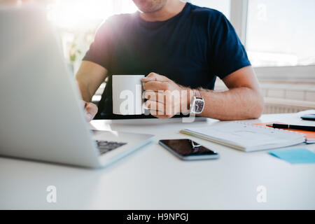 Cropped shot of young man with cup of coffee working on laptop. Business man working at his desk with coffee. Focus - Stock Photo