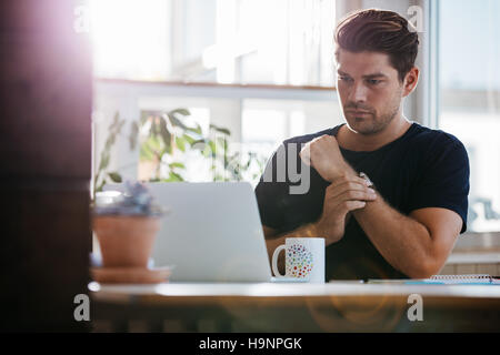 Shot of young man sitting at his desk and looking at a laptop. Businessman working in office. - Stock Photo