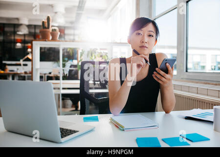 Portrait of confident asian woman sitting at her desk with mobile phone. Asian businesswoman working in office. - Stock Photo